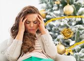 foto of sad christmas  - Portrait of frustrated young woman near christmas tree - JPG