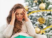 stock photo of sad christmas  - Portrait of frustrated young woman near christmas tree - JPG