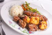 stock photo of gyro  - Mixed chicken lamb adana shish kebabs served served on gyro doner with rice pilaf and garnished with green vegetables - JPG