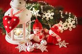 foto of home is where your heart is  - Cute couple of little adorable snowmen is standing near the white fairy lantern with a toy heart on it and decorated fir tree branch behind it - JPG