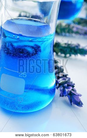 closeup of a flask with flower essence and a pile of lavender flowers