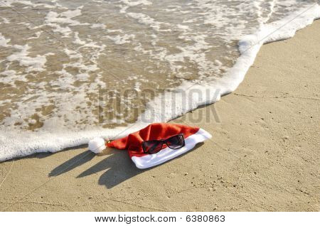 Santa Hat And Sunglass On The Sand.