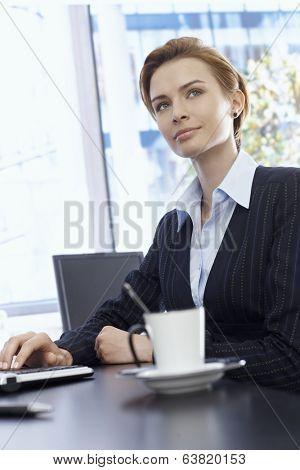 Portrait of beautiful blonde businesswoman sitting at desk, looking away.