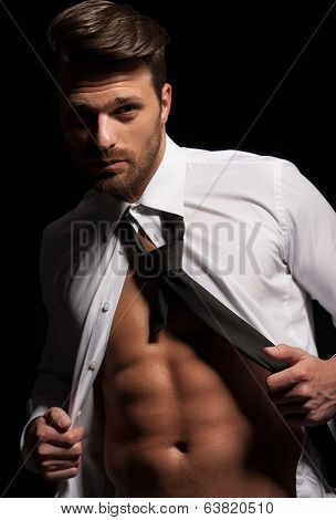 Man in suit showing abs due to hard workout