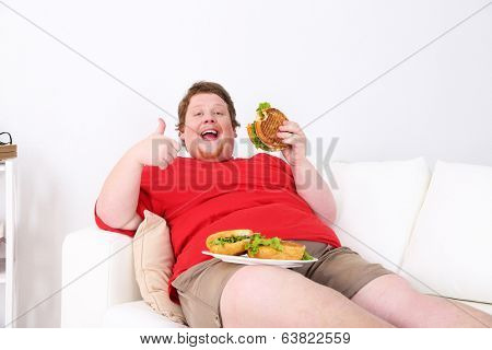 Fat man eating tasty sandwich on home interior background