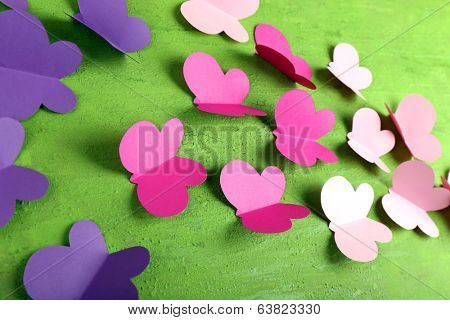 Paper cut out butterflies, on wooden background