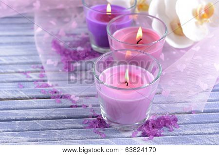 Beautiful colorful candles and  orchid flowers, on color wooden background