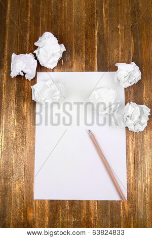 Sheet of white paper with crumpled  paper  and pencil on table close-up