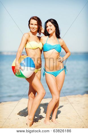 summer holidays, vacation and beach activities - girls in bikinis with ball on the beach