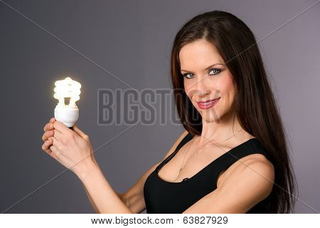 Attractive Smiling Brunette Woman Holding Green Energy Fluorescent Light Bulb