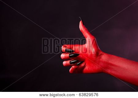 Spooky red devil hand with black nails showing thumbs up, studio shot on smoky background