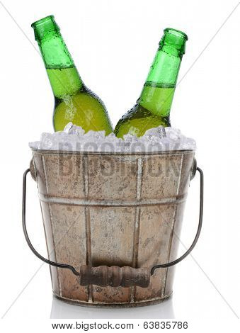 An old fashioned bucket filled with ice and beer bottles. Two green bottles of beer with caps removed are represented in vertical format on a white background with reflection.