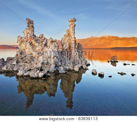 The magic of Mono Lake. Outliers - bizarre limestone formations reflected in the smooth water. Orange sunset