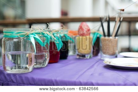 Colorful paints on palette with brushes ready for painting easter eggs
