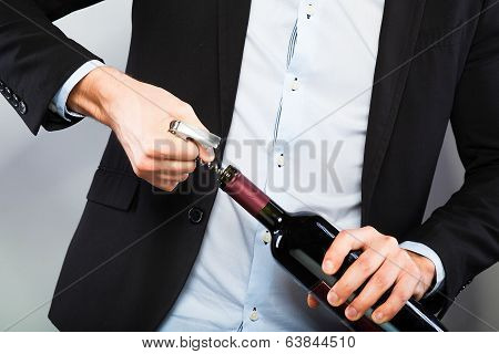 Handsome Man Opening Bottle Of Wine
