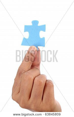Hand with blue jigsaw puzzle