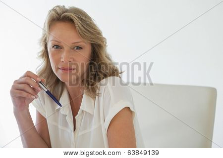 Casual businesswoman smiling at camera in her office