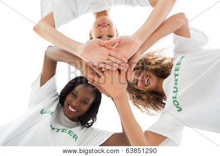 Happy volunteers putting hands together and looking down at camera on white background
