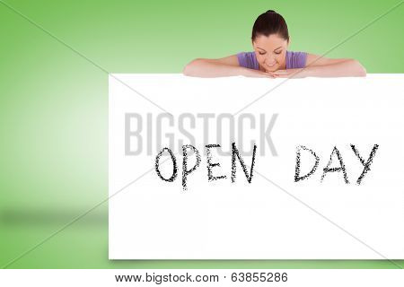 Pretty brunette showing card with open day against green background