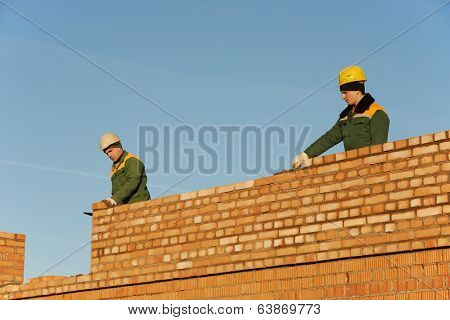 two construction mason worker bricklayer installing red brick with trowel putty knife outdoors