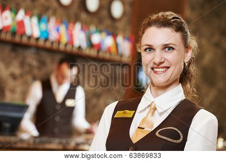 Happy receptionist female worker portrait standing at hotel counter in lobby