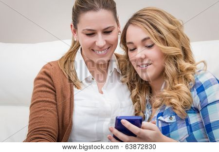 Mother and daughter laughing when looking at phone