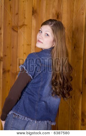 Woman Looking Over Shoulder By Wood