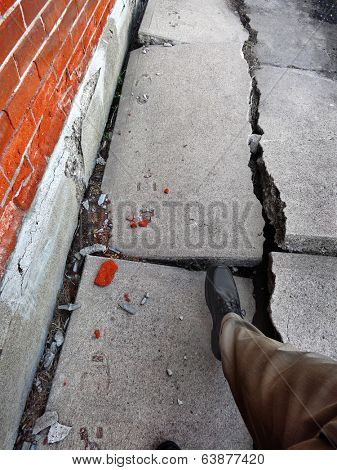 Man walking on broken dangerous cracked sidewalk