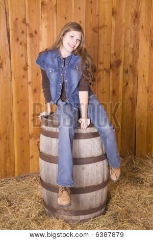 Woman Sitting On Barrel With A Smile