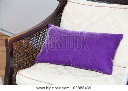 Purple pillow on wooden chair in house