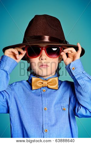 Portrait of a cute 7 year old boy wearing elegant hat and bow-tie with sunglasses.
