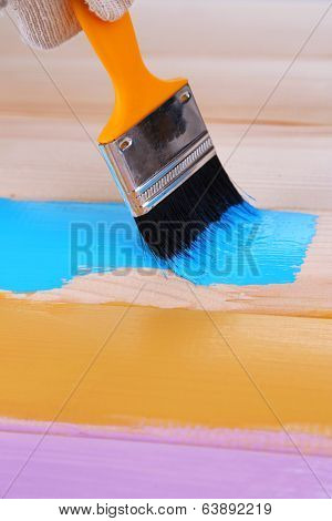 Brush painting wooden furniture, close up