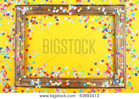 Photoframe with confetti on yellow background