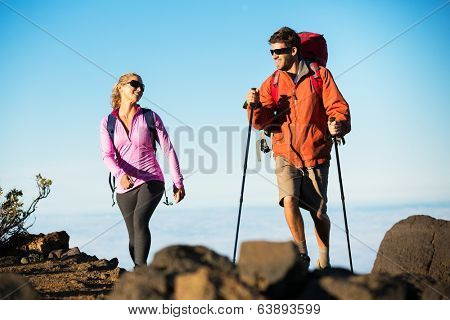Hiking in the mountains. Happy athletic couple with backpacks enjoying hike outdoors on beautiful mountain trail.