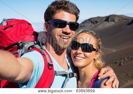 Happy couple taking photo of themselves with smart phone outdoors, Taking a