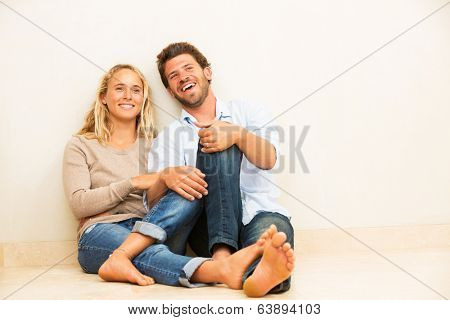 Happy young couple at home relaxing on the floor