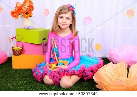 Beautiful small girl in petty skirt holding basket with colorful eggs on decorative background
