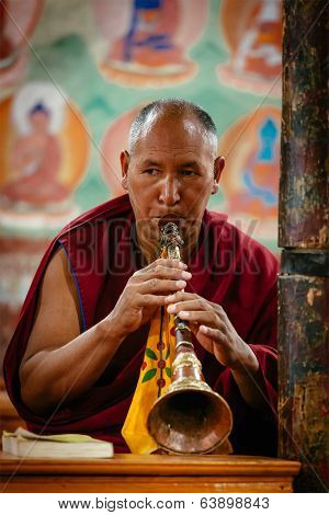 THIKSEY, INDIA - SEPTEMBER 4, 2011: Tibetan Buddhist monk playing religios music intstrument during prayer in Thiksey gompa (Buddhist monastery)  of Gelugpa sect - the largest gompa in central Ladakh