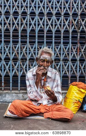 TIRUCHIRAPALLI, INDIA - FEBRUARY 14, 2013: Unidentified old Indian man eating in the street