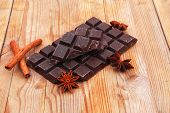 stock photo of love bite  - split bar of dark chocolate on wooden table - JPG