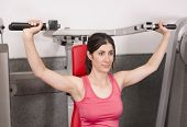 foto of spandex  - Woman posing in gym room ready for shoulder fitness exercises - JPG