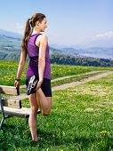 stock photo of stretching  - Photo of a young woman stretching her leg before she starts to run on a country path. City and lake in the distance.