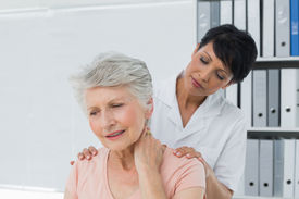 picture of chiropractor  - Female chiropractor looking at senior woman with neck pain in the medical office - JPG