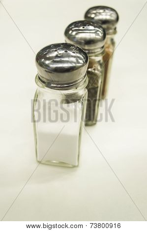 Close Up Salt, Pepper, And Barbecue Classic Shakers On White Background