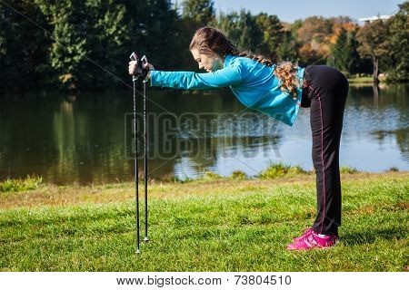 Nordic walking adventure and exercising concept - woman doing exercise with nordic walking poles in park