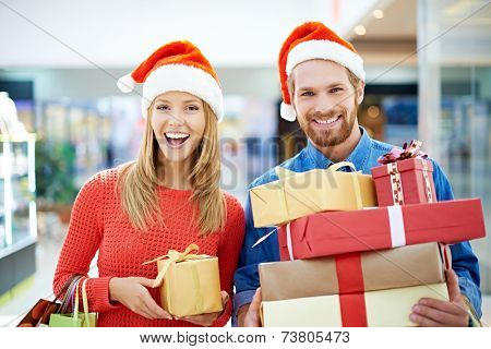 Happy couple of shoppers buying Christmas presents