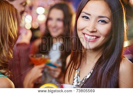 Joyful Asian girl at a party, her friends in the background
