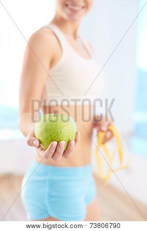 Sporty female giving green apple