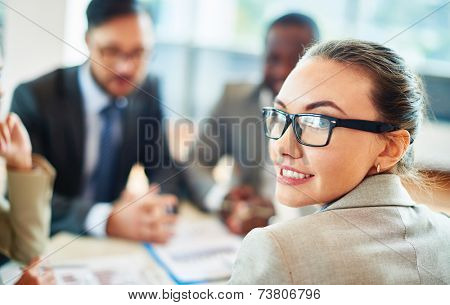Portrait of beautiful secretary in eyeglasses looking at camera on background of co-workers