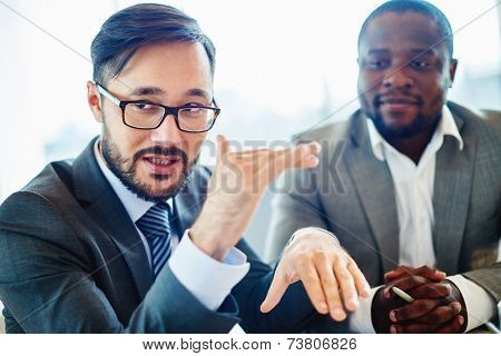Serious businessman of Asian ethnicity explaining his ideas to colleagues